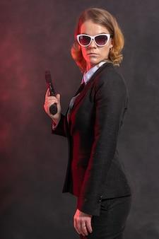 Kobieta mafijna z bronią w ręku. portret na ciemnej ścianie z czerwonym światłem.