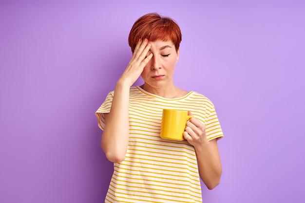 Kobieta mająca ból głowy, trzymając kubek w dłoniach, źle się czuje. na białym tle na fioletowej ścianie
