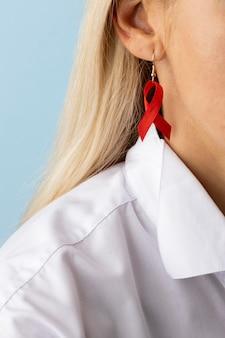 Kobieta mająca kolczyk z symbolem światowego dnia pomocy