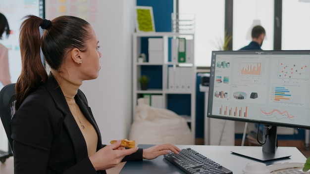 Kobieta mająca zamówienie dostawy jedzenia na biurku podczas lunchu na wynos, pracująca w biurze firmy biznesowej