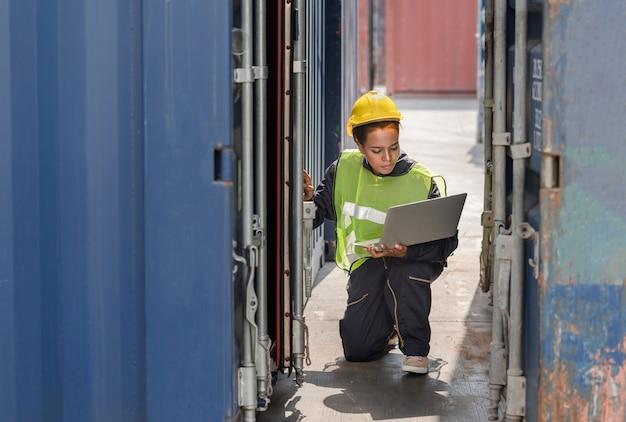 Kobieta majster sprawdzanie numeru na drzwiach skrzynki kontenerów z laptopem
