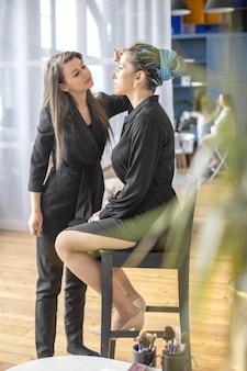 Kobieta make-up master stosująca puder do pudru na twarz w salonie kosmetycznym