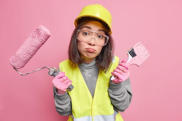 Kobieta malarka wygląda nieszczęśliwie torebki usta trzyma pędzel i wałek do malowania ubrana w mundur idzie do remontu domu
