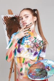 Kobieta malarka zabrudzona kolorową farbą rysuje na płótnie