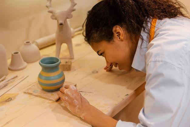 Kobieta malarstwo gliniany garnek z bliska