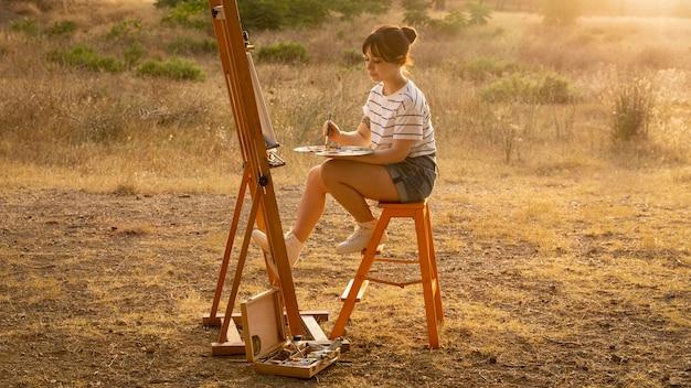 Kobieta malarstwo na płótnie na zewnątrz w przyrodzie