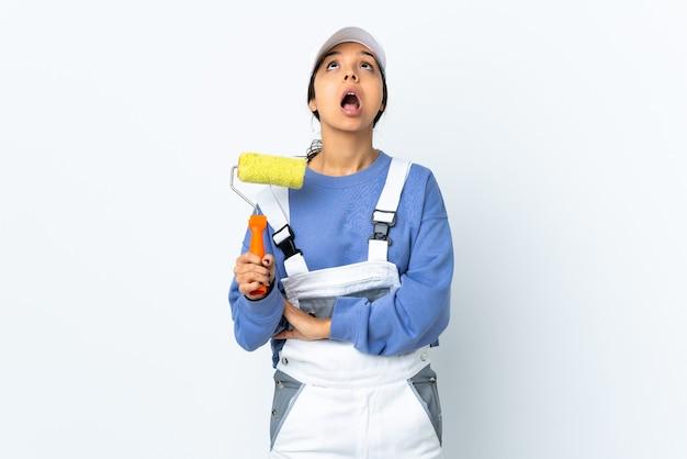 Kobieta malarz na białym tle ściany patrząc w górę iz zaskoczonym wyrazem