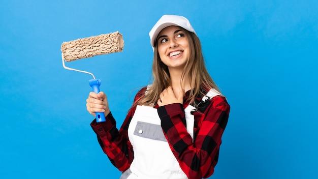 Kobieta malarz na na białym tle niebieski patrząc z uśmiechem
