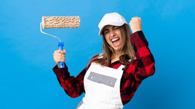 Kobieta malarz na niebieską ścianą świętuje zwycięstwo