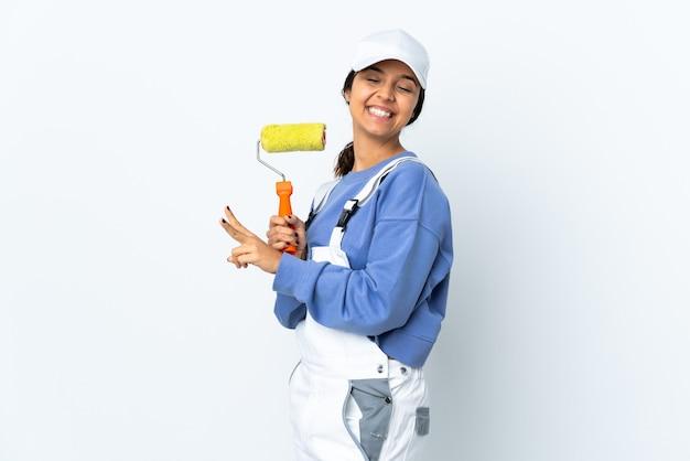 Kobieta malarz na odizolowanej białej ścianie, uśmiechając się i pokazując znak zwycięstwa