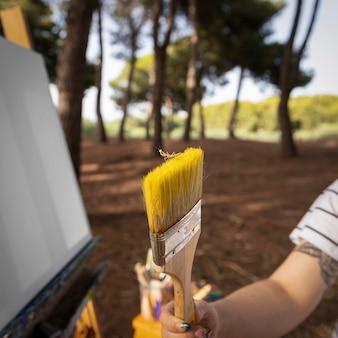Kobieta malarz na zewnątrz trzymając pędzel
