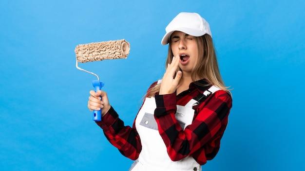 Kobieta malarz nad odosobnioną niebieską ścianą ziewanie i obejmowanie ręką szeroko otwarte usta