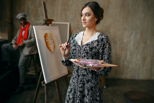 Kobieta malarz portret i model w studio sztuki. artystka stojąca w swoim miejscu pracy, słodka kreatywna mistrzyni w warsztacie, kreatywność pędzlem