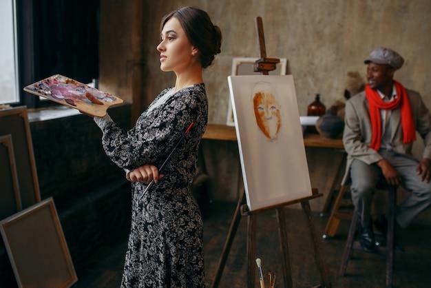 Kobieta malarz portretowy trzyma paletę i pędzel, męski model w studio sztuki. mężczyzna artysta stojący w swoim miejscu pracy, kreatywny mistrz w warsztacie