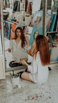 Kobieta malarz siedzi na podłodze przed lustrem. wnętrze pracowni artystycznej. materiały do rysowania, farby olejne, pędzle artystyczne