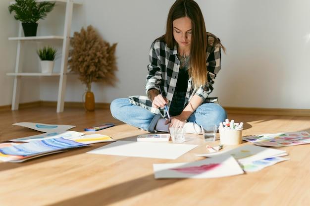 Kobieta malarz siedzi na podłodze
