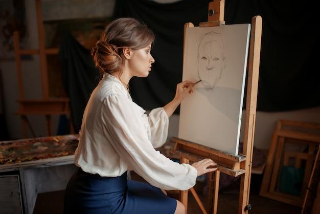 Kobieta malarz w studio, szkic ołówkiem na sztalugach