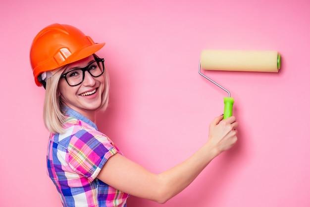 Kobieta malarz za pomocą wałka do renowacji kolor różowej ściany indoor.smiling architekt projektant kobieta w biznesie kraciaste koszule na sobie kask budowniczy malowanie ścian w mieszkaniu.