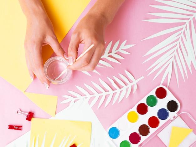 Kobieta malowanie filiżanki farbą akwarelową
