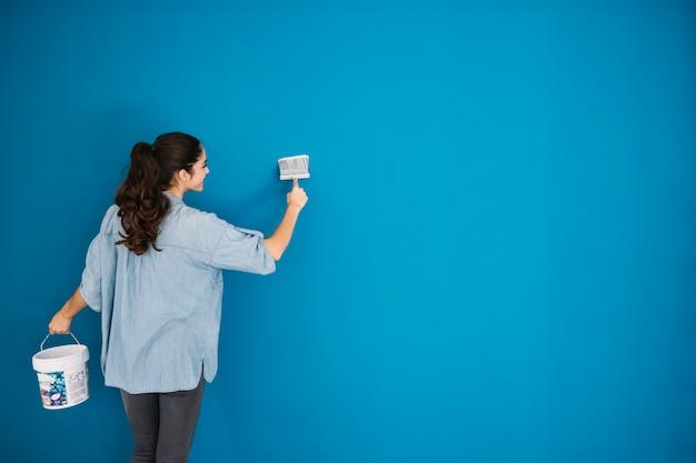 Kobieta malowanie niebieskiej ściany