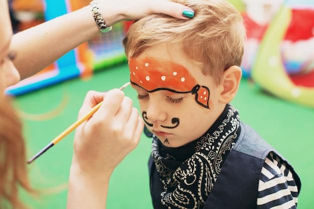 Kobieta malowanie twarzy dziecka na imprezie z okazji halloween