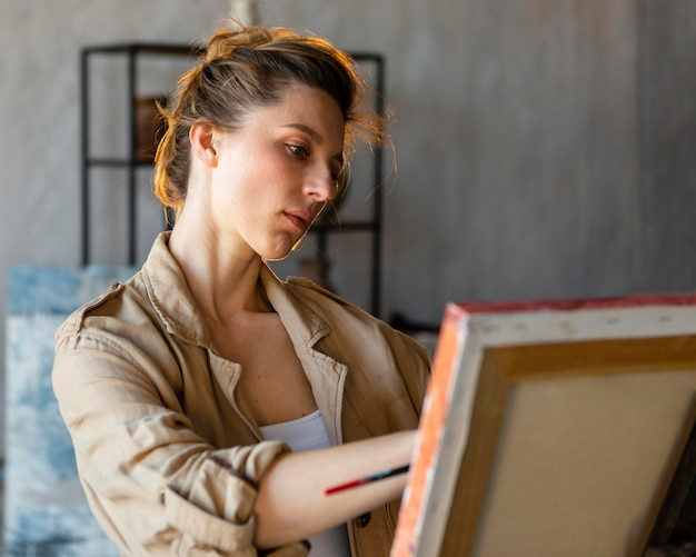 Kobieta malująca na płótnie średni strzał