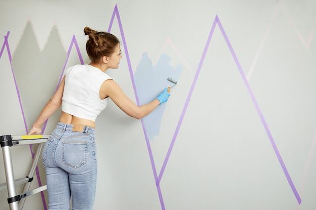 Kobieta malująca ścianę niebieską farbą i wałkiem za pomocą taśmy maskującej stojąc na drabinie