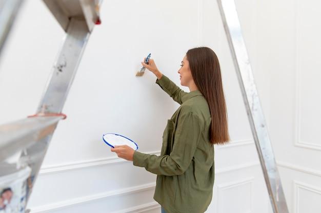 Kobieta malująca ścianę średni strzał