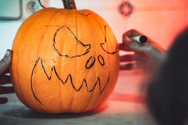 Kobieta malująca twarz z dyni i robiąca stronę z latarnią na halloween