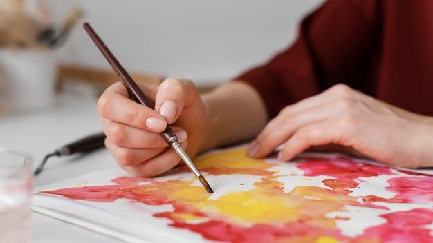 Kobieta maluje akwarelami na papierze