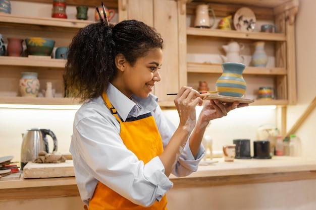 Kobieta maluje gliniany garnek w pomieszczeniu