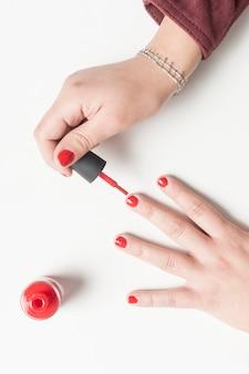 Kobieta maluje jej gwoździe w czerwieni. powyżej widoku