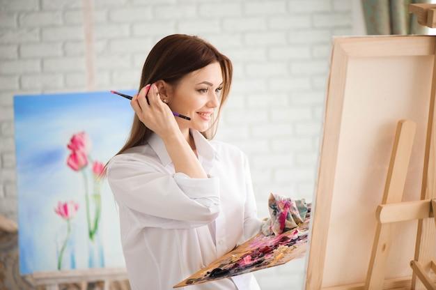 Kobieta maluje obraz na płótnie farbami olejnymi w swoim studio