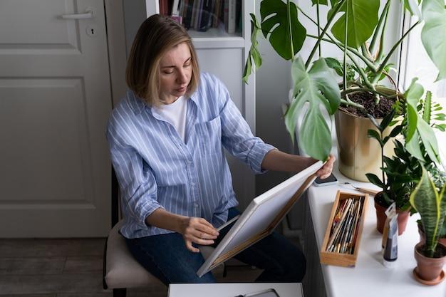 Kobieta maluje obraz na płótnie i robi szkice ołówkiem siedząc przy oknie w domu podczas blokady