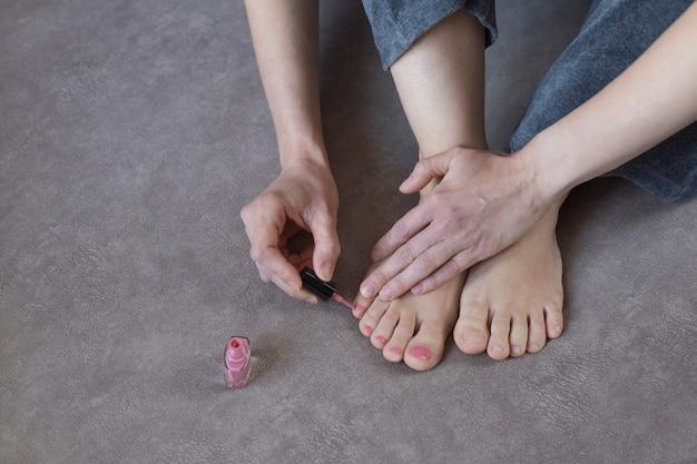 Kobieta maluje paznokcie różowym lakierem do paznokci. pedicure rano w domu