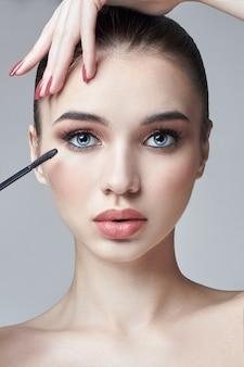 Kobieta maluje rzęsy pędzelkiem do rzęs. zwiększenie objętości rzęs, kosmetyki do pielęgnacji oczu. piękna twarz kobiety. profesjonalny makijaż własnymi rękami
