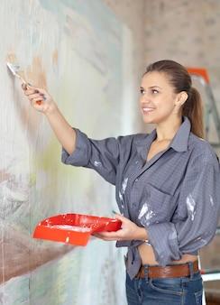 Kobieta maluje ścianę pędzlem