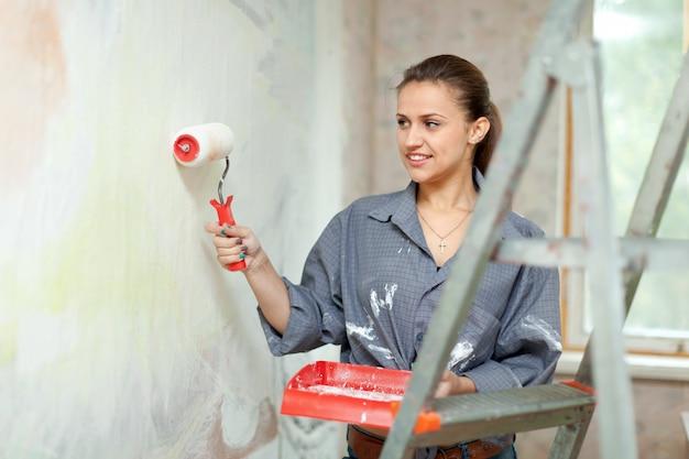 Kobieta maluje ścianę z rolki w domu