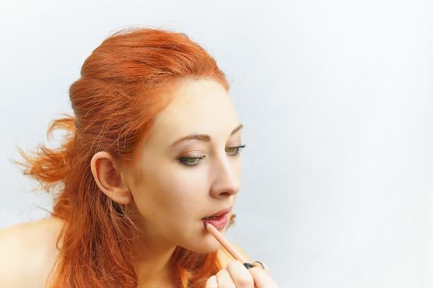 Kobieta maluje usta.