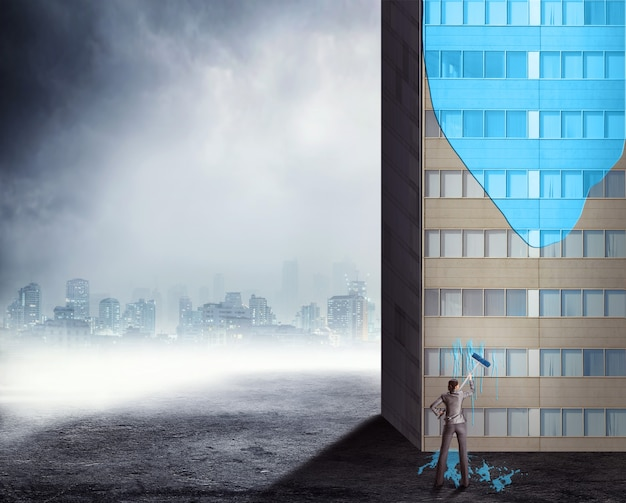 Kobieta maluje wysoki biurowiec w kolorze niebieskim