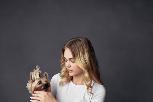 Kobieta mały pies zabawy studio ciemne tło