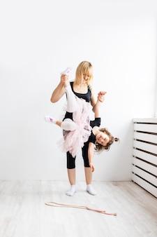 Kobieta mama oddaje się tańcu z córeczką, uprawia gimnastykę w białym wnętrzu