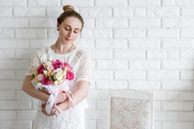 Kobieta marzeń z prezentem. bukiet luksusowych kwiatów. kolorowe róże bokserskie w różowym pudełku w kształcie walca. piękny i zmysłowy prezent na 8 marca, walentynki