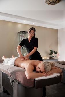 Kobieta masująca swojego klienta w swoim salonie
