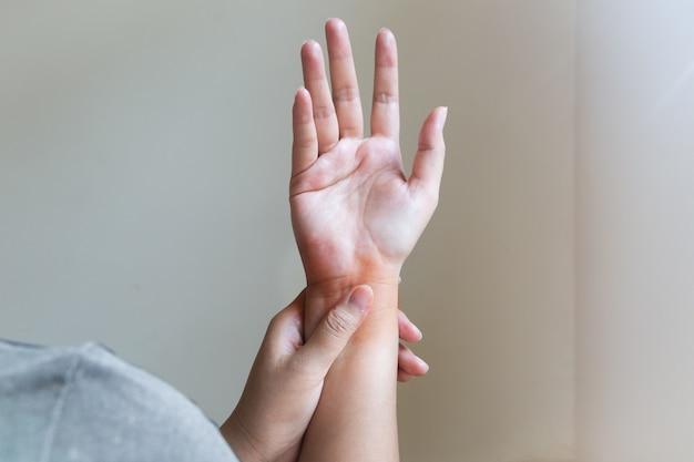 Kobieta masuje bolesną rękę. pojęcie opieki zdrowotnej i medycznej.