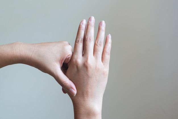 Kobieta masuje jej bolesną rękę i palec