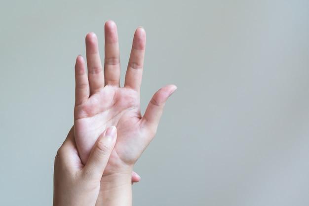 Kobieta masuje jej bolesną rękę i rękę na rękę