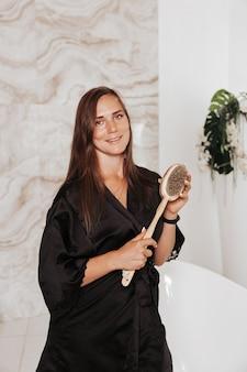 Kobieta masuje skórę nóg suchą szczoteczką do masażu w łazience. dziewczyna walczy z cellulitem