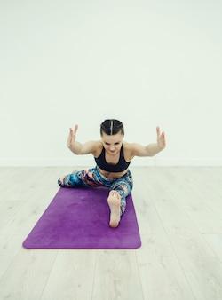 Kobieta matę do jogi, rozciąganie w pokoju
