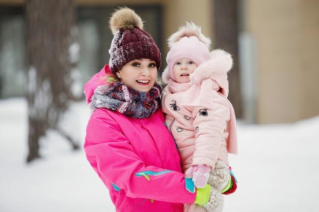 Kobieta matka trzyma córkę w ramionach w śnieżnym parku w zimie na zewnątrz.